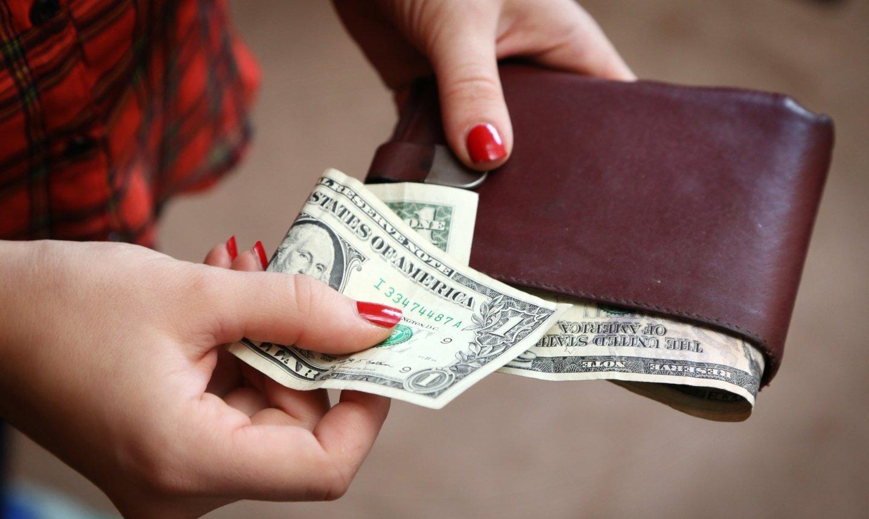 Personne tenant un portefeuille avec des billets d'un dollar